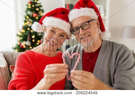 christmas, holidays and people concept - close up of happy smiling senior couple in santa hats with candy canes at home