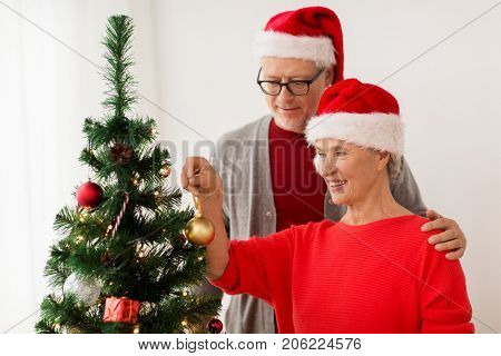 holidays and people concept - happy smiling senior couple in santa hats decorating christmas tree at home