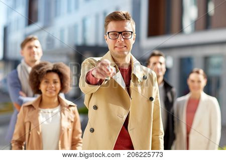 business, leadership and hiring concept - man pointing finger at you over international group of people on city street