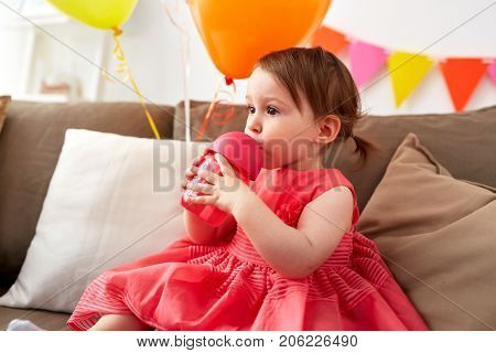 childhood, people and holidays concept - baby girl drinking from sippy cup or bottle at home birthday party