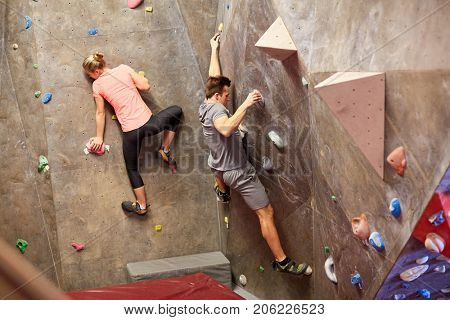 fitness, extreme sport, bouldering, people and healthy lifestyle concept - man and woman exercising at indoor climbing gym wall