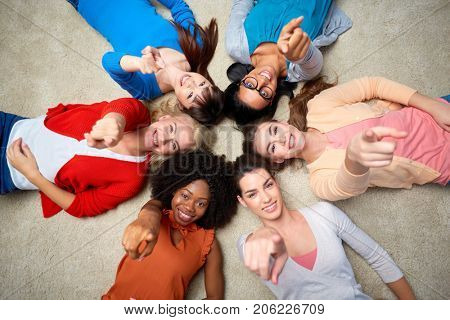 diversity, race, ethnicity and people concept - international group of happy smiling different women lying on floor in circle and pointing finger at you