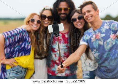 summer holidayds, technology and people concept - smiling young hippie friends in sunglasses taking picture by smartphone on selfie stick in countryside