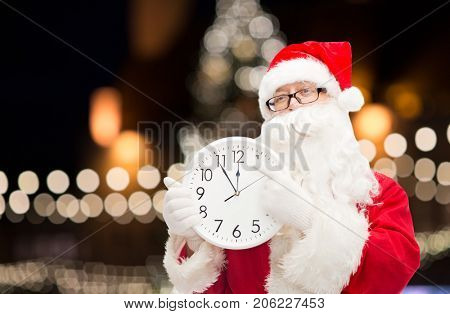 christmas time, holidays and people concept - santa claus with clock pointing finger to twelve