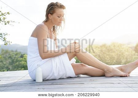 Woman applying body lotion, outdoor bathtime