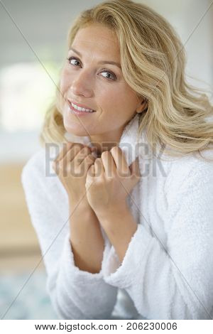 Portrait of beautiful 40-year-old woman relaxing in bathrobe at home