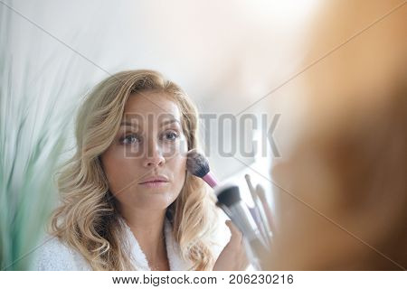 Portrait of 40-year-old woman applying makeup on - mirror view
