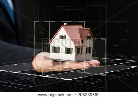 architecture, building, construction, real estate and property concept - close up of businessman or architect hand holding house model over black background