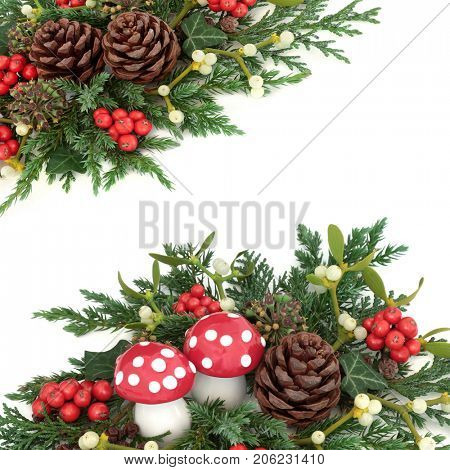 Winter and christmas background border with  fly agaric mushrooms, holly, mistletoe, ivy, cedar and juniper leaf sprigs and pine cones on a white.