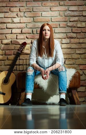 Ginger girl sitting by brick wall having guitar.