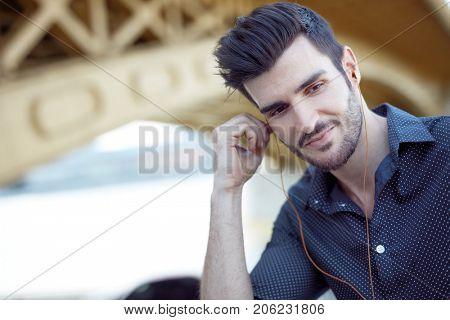 Young man enjoying music through earbuds under bridge outdoors.