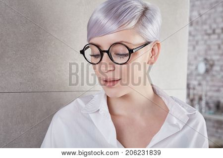Portrait of retro style woman with lilac hair looking down, wearing black framed glasses.