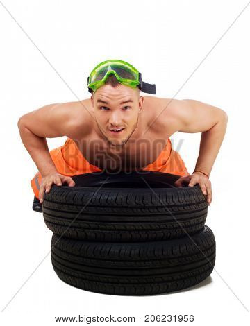 man dressed as car mechanic with tools and tire, isolated against white background