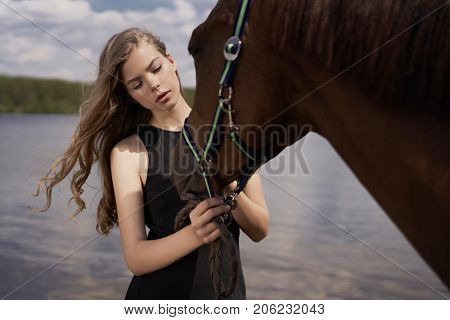 Outdoor art fashion photo of beautiful young lady with horse.