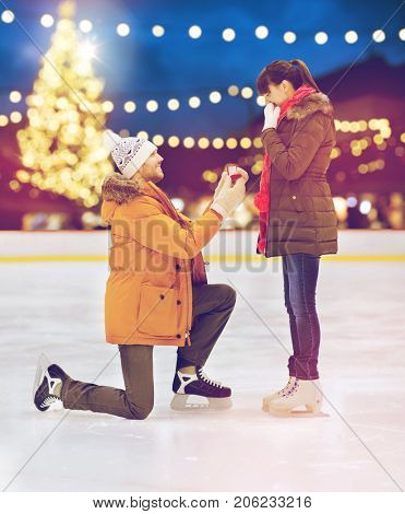 love, holidays and relationships concept - happy couple with engagement ring at outdoor skating rink over christmas lights background