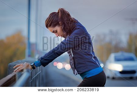 Athletic woman resting after jogging and leaning on a parapet of the bridge. Beautiful young woman relaxing after a jog in the winter early morning. Sport girl rest after a long run in the city.