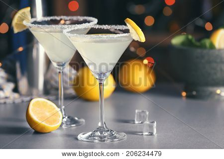 Glasses with tasty lemon drop martini cocktail on table
