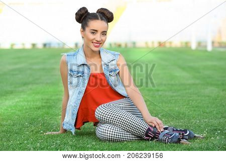 Young roller skater sitting on green grass