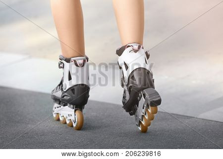 Legs of young woman rollerskating outdoors