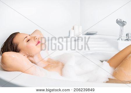 Young Woman Enjoying Bathing In Bathtub