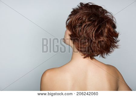 Beautiful young woman with short pixie haircut with her back to the camera on the grey studio background
