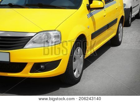 Bright yellow taxi cab on city street