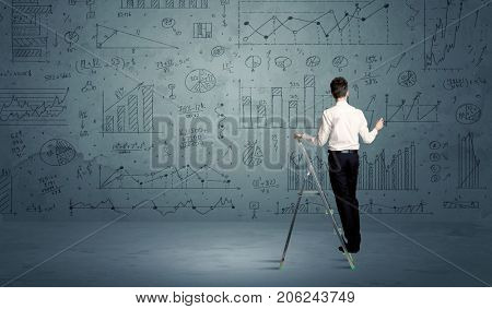 A businessman in modern stylish elegant suit standing on a small ladder and drawing pie and block charts on grey wall background with exponential progressing curves, lines, circles, , blocks, numbers