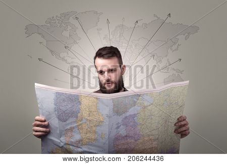 Handsome young man holding a map with world map and arrows behind him