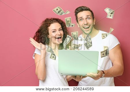 Money flying out of laptop while couple using it on color background