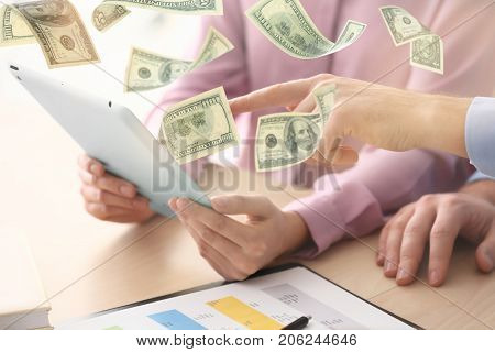 Money flying out of tablet while people using it at table in office