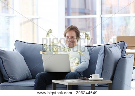 Money flying out of laptop while mature man using it at home