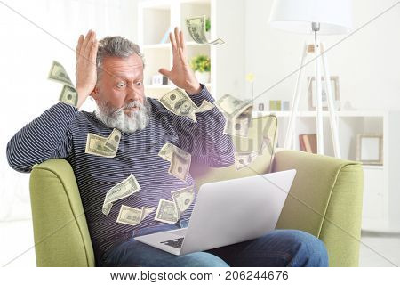 Money flying out of laptop while senior man using it at home