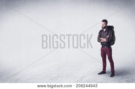 Standing handsome young man with a backpack