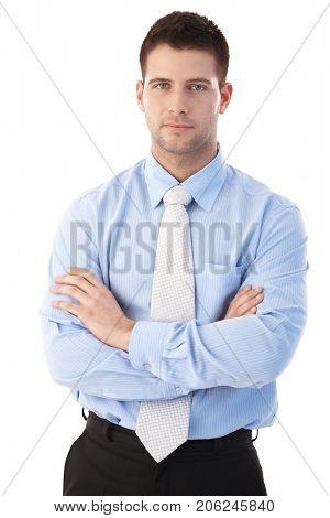 Businessman portrait. Confident young businessman standing arms crossed. Businessman portrait over white background.