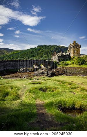 Gorgeous sun kissed vertical view of Eilean Donan Castle on a bright summer's day.