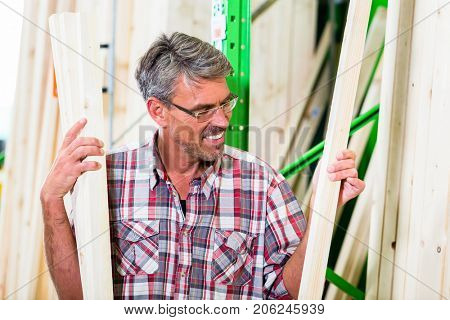 Customer in lumber department of hardware store choosing wood strip for DIY-project