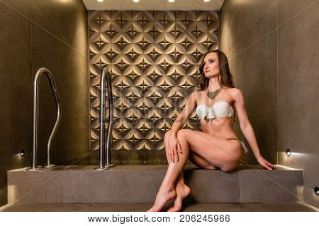 Beautiful young woman wearing elegant swimwear and a golden necklace while daydreaming in a luxury wellness center