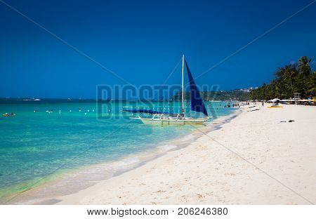 Philippine traditional boat with blue sail on White Beach. Boracay Island, Philippines.