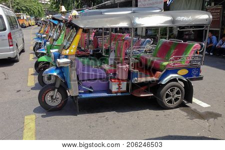 BANGKOK THAILAND - SEPTEMBER 27 2017:The three wheeled tuk tuk taxi wait passenger on a street in the Thai capital on September 27 2017 in Bangkok Thailand. Tuk tuks are commonly used in transporting people.