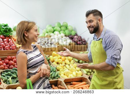 Salesman helping customer choosing vegetables at market