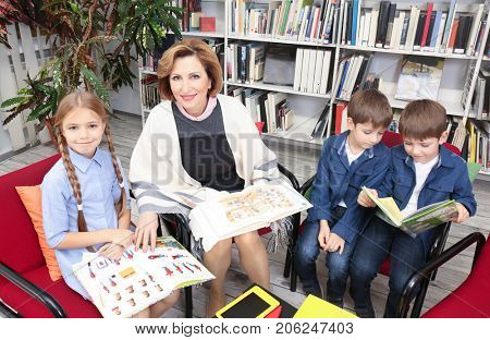 Teacher and schoolchildren with books at library