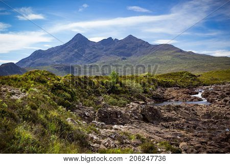 Mountain peaks of Cuillin and a meandering stream landscape  at Tir Nan Iolaire or the Land of Eagles on the Isle of Skye in Scotland.