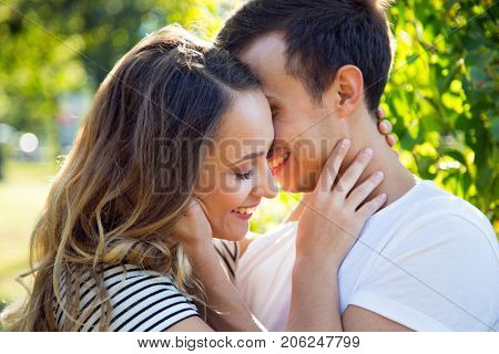 Portrait of a happy couple hugging in a park in sunny day