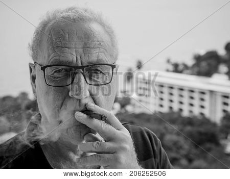 Black and white portrait of an elderly man who smokes a cigar. Close-up