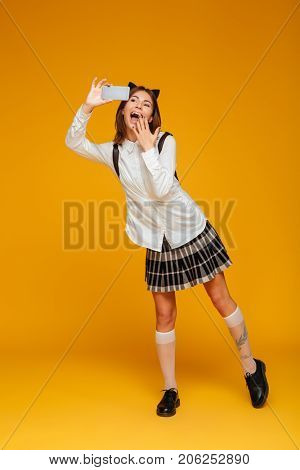 Full length portrait of a surprised happy teenage schoolgirl in uniform with backpack taking a selfie while standing isolated over orange background