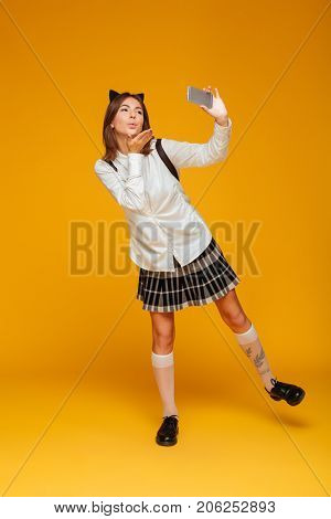 Full length portrait of a cute teenage schoolgirl in uniform with backpack taking a selfie while standing and sending air kiss isolated over orange background