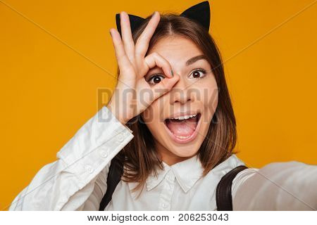 Close up portrait of a funny teenage schoolgirl in uniform with backpack taking a selfie while standing and looking through her fingers isolated over orange background