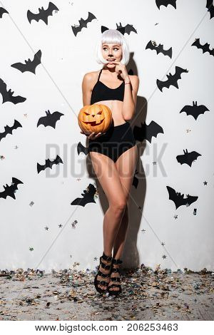 Full length portrait of a beautiful playful woman in halloween cat costume posing with carved pumpkin over bats and confetti background