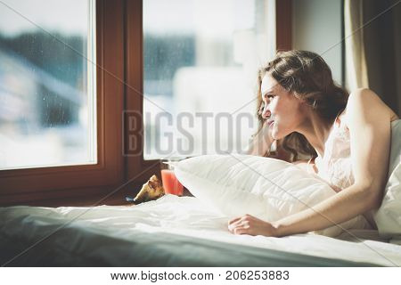Woman lying in bed at early morning near window.