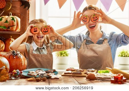 Mother and her daughter having fun at home. Happy Family preparing for Halloween. Mum and child cooking festive fare in the kitchen.